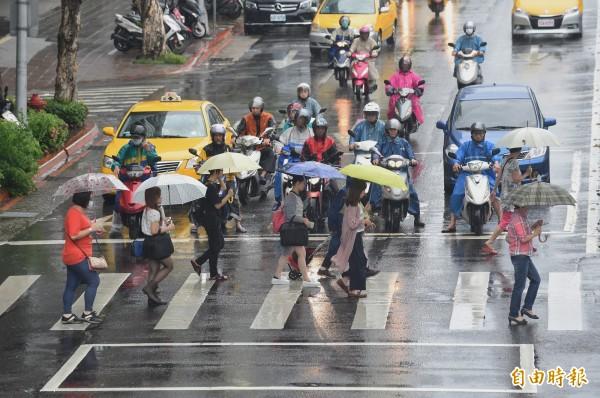北市今正常上班上課,通勤族冒雨上班。示意圖。(記者劉信德攝)