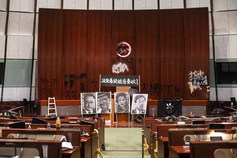 香港立法會預計下月16日可復會。圖為7月1日晚間示威者衝入立法會,於主席台掛出「沒有暴徒只有暴政」布條,並擺出林鄭月娥等共4名港府高層的黑白照。(彭博)