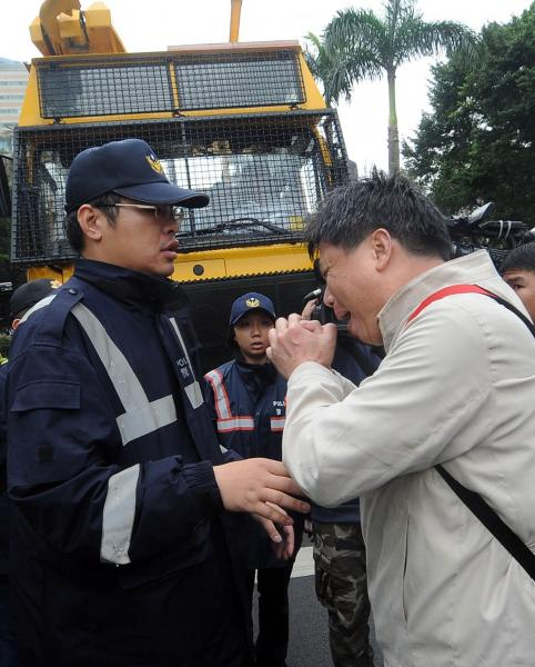 政大教授徐世榮(右)上午擋在警方噴水車前拜託警方不要再對學生噴水。(記者王敏為攝)