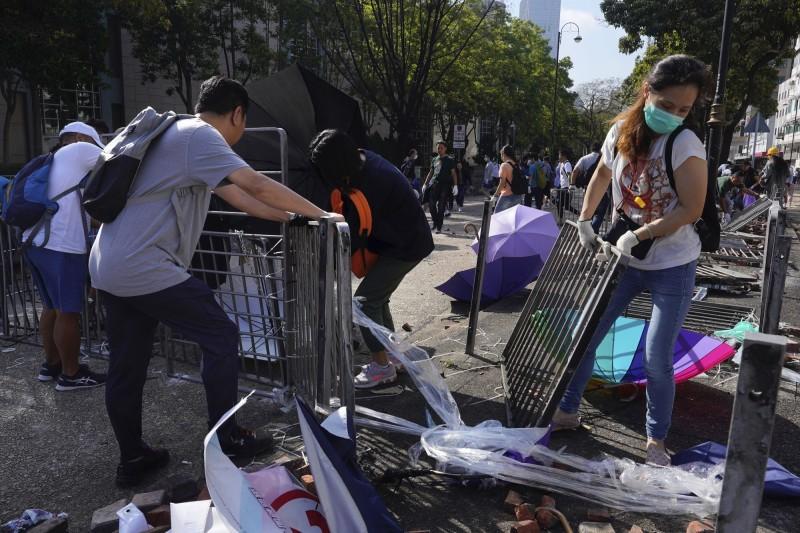 今早陸續有香港民眾在各地清理路障或雜物。圖為民眾於香港理工大學周邊清理路障。(美聯社)