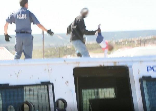 抗議拆遷的男子在屋頂上將自己的1歲女兒拋下樓,遭到警方逮捕。(圖擷取自臉書)