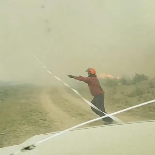一群消防隊員拉著消防水帶欲撲滅「火龍捲」,沒想到火龍捲吸走消防隊的消防水帶。(路透)