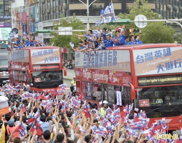 吉普車、遊覽車載著選手們從總統府出發,不少民眾手拿「台灣英雄」旗幟與國旗夾道歡迎,氣氛熱烈。(記者黃耀徵攝)