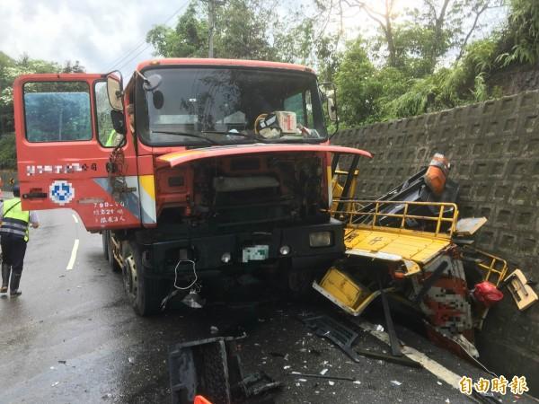 失控衝入對向車道的大型拖板車,撞到停放路旁施工的工程車,工程車被撞進水溝,當場夾扁,所幸車上無人。(記者佟振國攝)