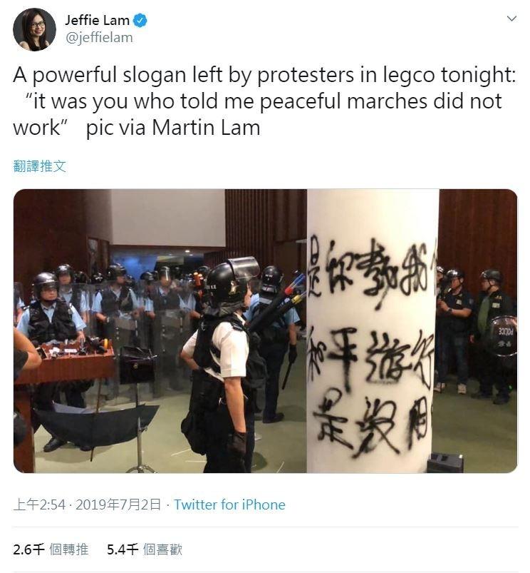 示威者散去後,一名香港警員看著柱子上以噴漆寫下的「是你教我們和平遊行是沒用的」。(擷取自Twitter@jeffielam)