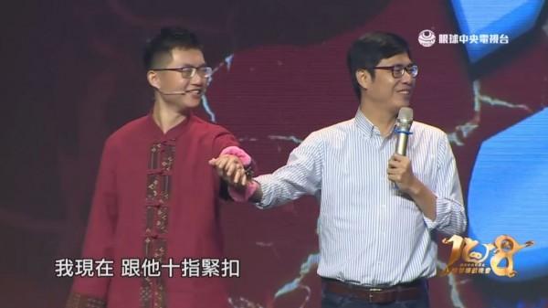 陳其邁出席「春晚聯歡晚會」,玩趣味競賽與主播銬上手銬十指緊扣。(圖擷取自眼球中央電視台)