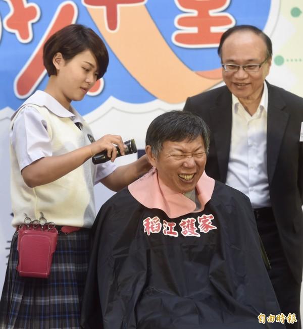 台北市長柯文哲9日出席「職人十堂」技職教育系列活動,體驗稻江護家同學剪髮技能。(記者簡榮豐攝)