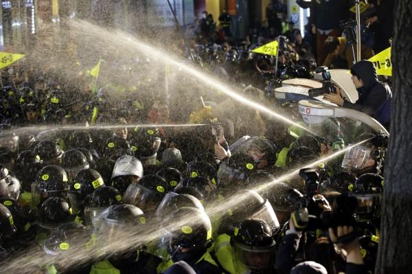 警方人員向抗議群眾噴灑液體試圖驅離。(美聯社)