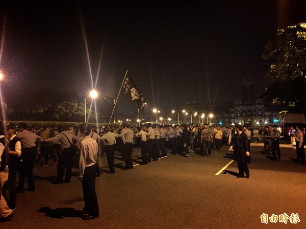 部份警力以手牽手的方式排成人龍,引導抗議民眾離開總統府前方的道路。(記者吳張鴻攝)