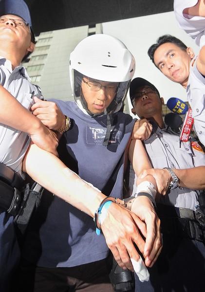 台北市街頭22日上午驚傳情殺案,造成林姓女子身亡,29歲兇嫌張彥文今(23)日傍晚押解回警局,身上仍看得到自戕造成的傷口。(記者方賓照攝)