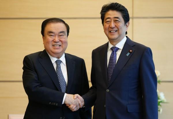 日本首相安倍晉三(右)今日與南韓特使、國會議員文喜相舉行會談,雙方就恢復日韓領袖每年一次互訪的「穿梭外交」達成共識。(法新社)