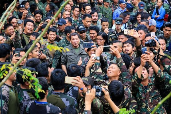 菲總統杜特蒂親赴戰場勉勵前線官兵,向他們保證,只要打完這場仗,就可以攜家帶眷免費遊香港。(路透)