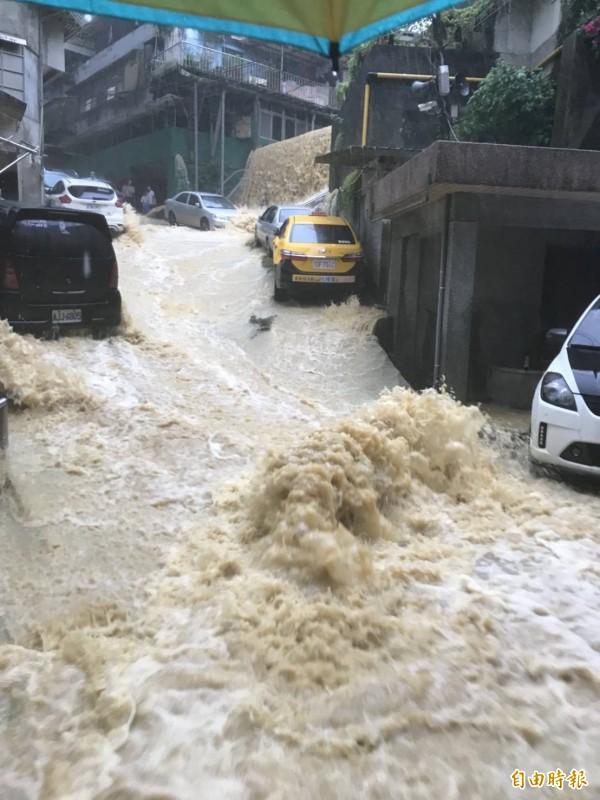 今天早上一場大雨,基隆市新西街207巷積水處處,泥水直衝擋土牆到下方,宛若瀑布,居民戲稱我家門前就有「十分瀑布」。(記者俞肇福攝)