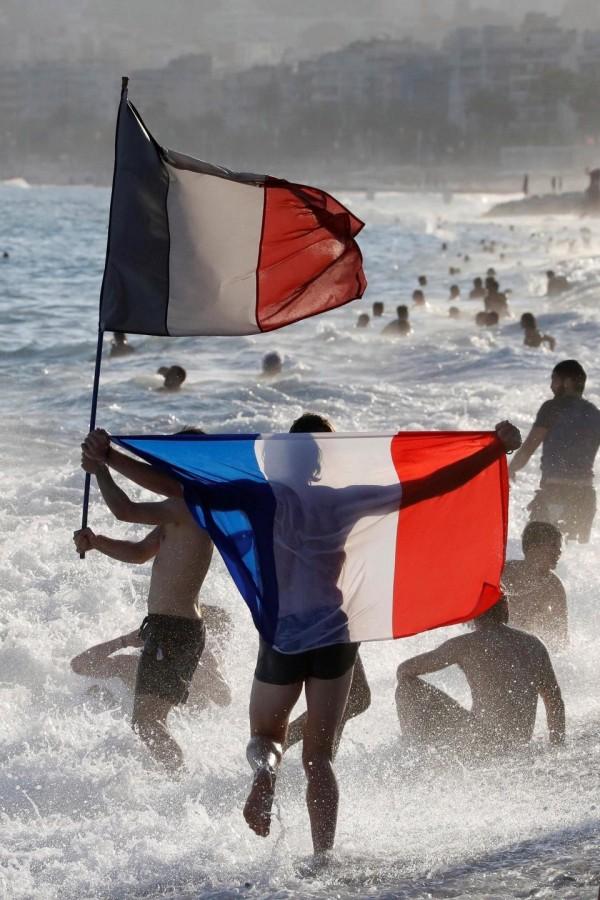 各地都有民眾拿著法國國旗奔跑。(路透)