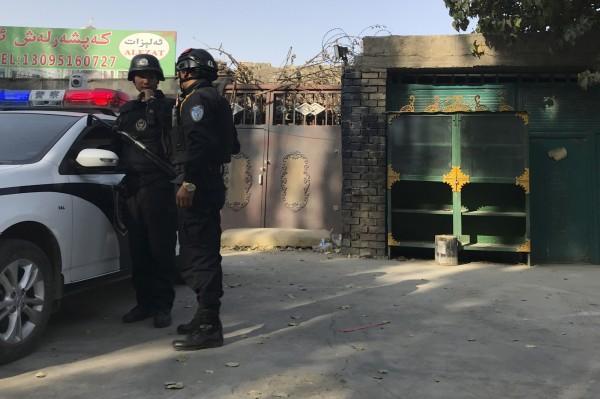 2017年11月2日,新疆庫爾勒市,警察站在一個被認為用於再教育的中心附近。(美聯社)