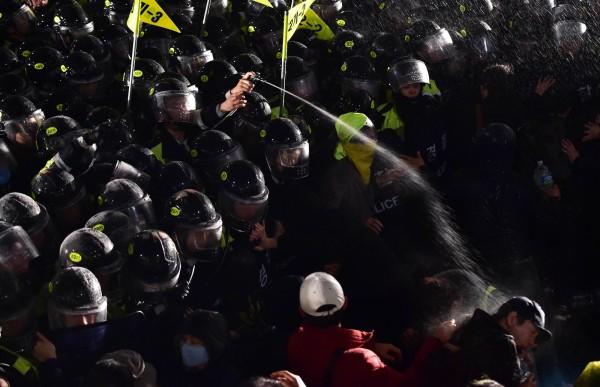 南韓民眾在光化門廣場前抗議世越號事件,警方躲在人牆後噴灑辣椒噴霧,試圖驅散群眾。(法新社)