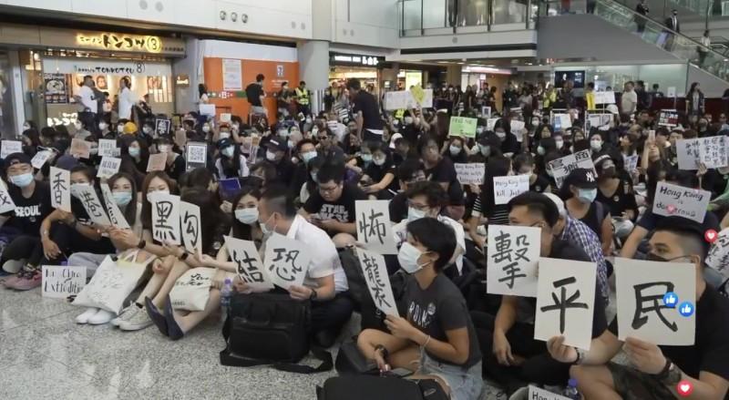 群眾手持「抗議香港警黑勾結恐怖襲擊平民」標語,抗議日前發生於香港元朗地區的暴力事件。(擷取自《立場新聞》直播畫面)