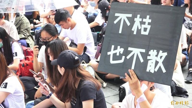 現場民眾舉起抗議標語,抗議香港政府強硬的手段。(記者胡姿霞攝)