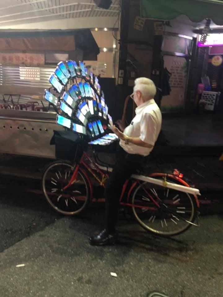 阿伯在中秋假期最後一天、15日晚間在街頭被捕獲身影,腳踏車上裝了45支智慧型手機。(圖擷取自爆廢公社)