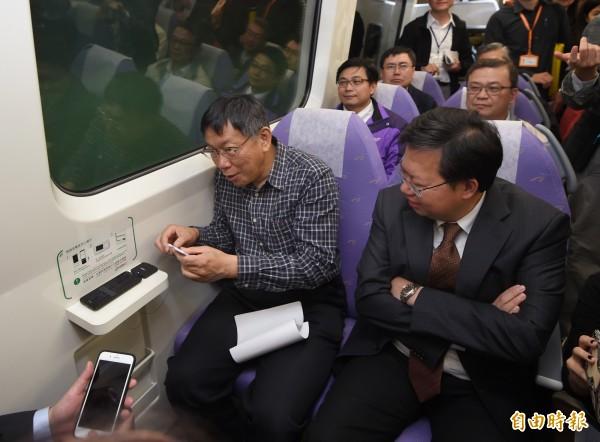 台北市長柯文哲15日參觀機場捷運,試用列車上手機無線充電。(記者方賓照攝)