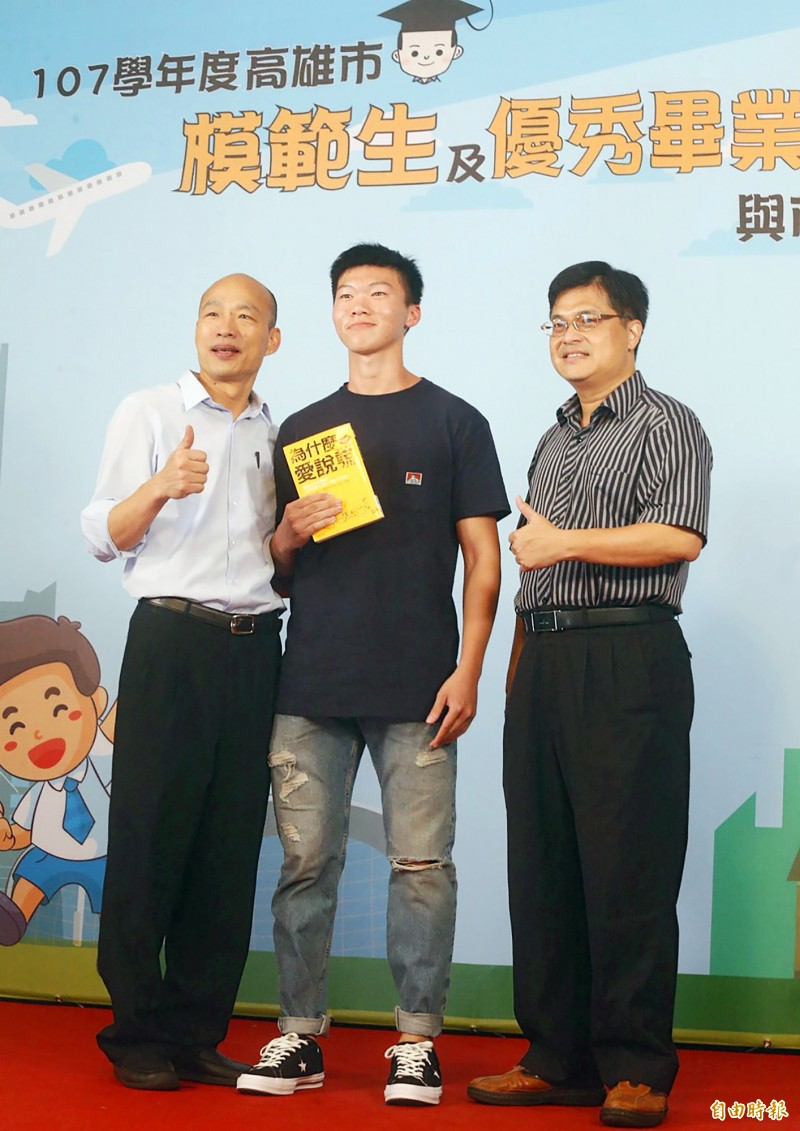 Kaohsiung Mayor Han Kuo-yu, left, poses with a Kaohsiung Senior High School student holding a copy of the Chinese edition of Brian King's The Lying Ape on Monday at an event for outstanding graduating students. Photo: Chang Chung-yi, Taipei Times