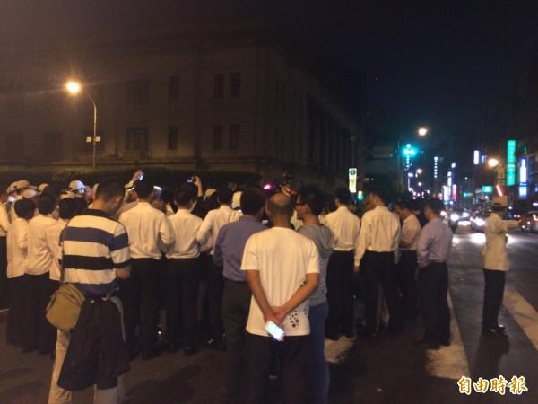 約有30多名學生衝到總統府前靜坐抗議,現場也出現許多穿著白衣的憲兵人員。(記者劉慶侯攝)