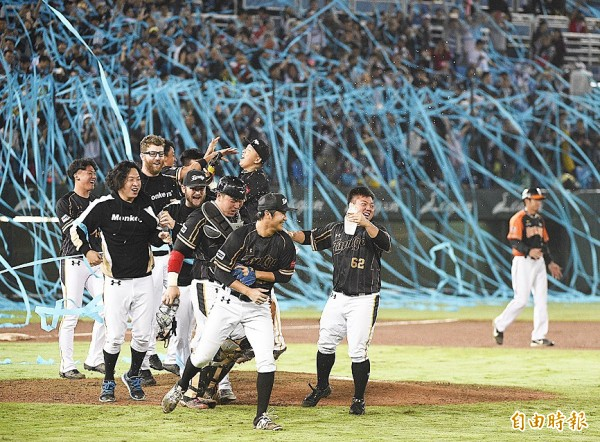 Lamigo Monkeys players celebrate winning the CPBL championship two years in a row after beating the Uni-President Lions 10-3 in Game 5 of the Taiwan Series at the Taoyuan International Stadium yesterday. Photo: Chen Chih-chu, Taipei Times Photo: Chen Chih-chu, Taipei Times
