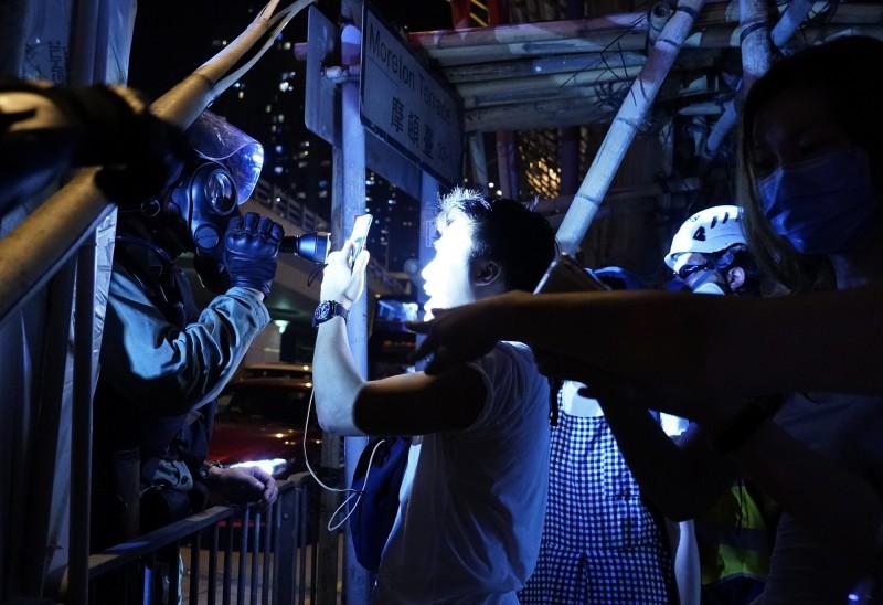 有記者昨晚遭警員攔查,警方非但不出示委任證,還以強光干擾記者採訪。圖僅示意。(美聯社)
