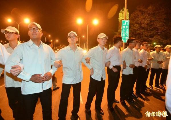現場出現身著白衣的憲兵人員手勾手保護總統府。(記者王藝菘攝)