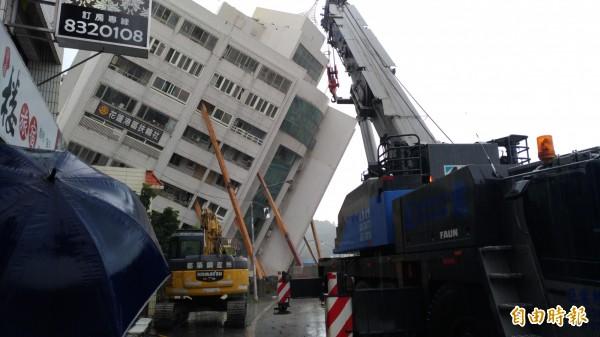 工程人員動用機具吊掛鋼樑消波塊穩定建物。(記者張議晨攝)