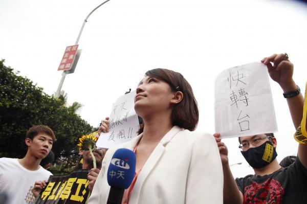 中天新聞台的記者準備進行連線報導,民眾在身後舉「請報導真相」、「快轉台」等標語抗議,記者表情無奈。(擷取自台大新聞E論壇臉書)