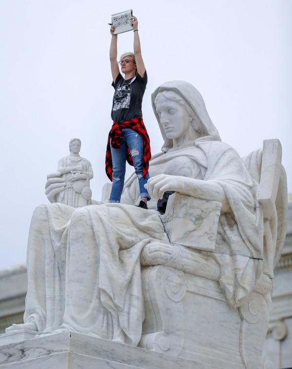 卡瓦諾經參議院投票通過,成為美國最高法院大法官,卡瓦諾宣誓就職的同時,一位女性抗議者爬上最高官法院的「正義女神」尖叫。(歐新社)