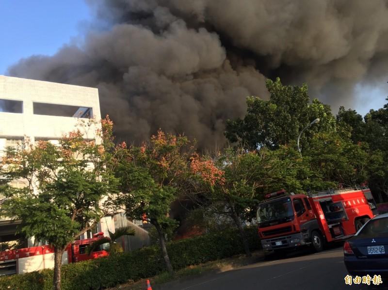 工廠大火濃煙不斷,消防局派分隊救火。(記者詹士弘攝)