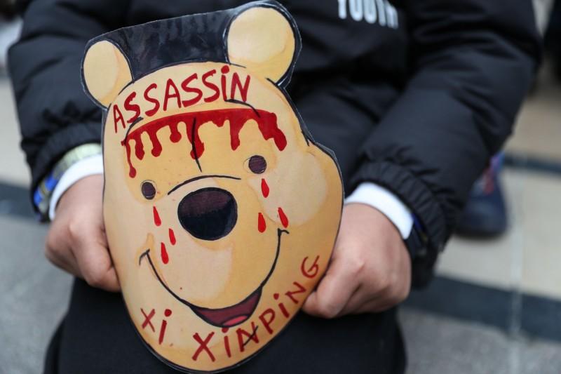 抗議者手持畫上血跡的維尼小熊面具,指控習近平是殺手。(法新社)