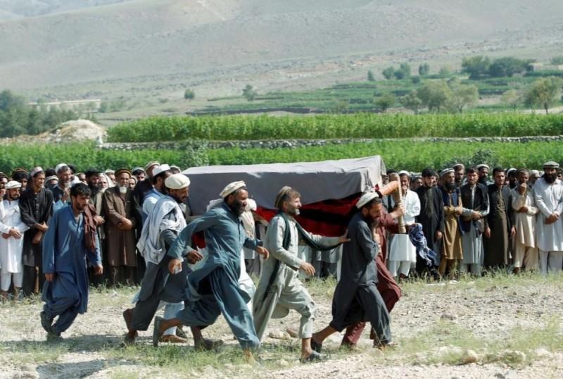 圖為男子們抬著受害者的棺木。(路透)