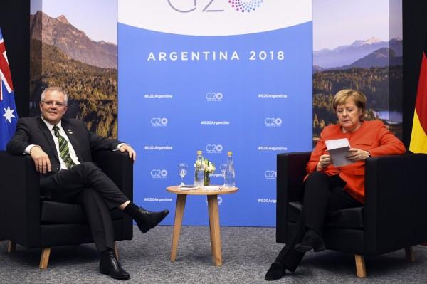 現任澳洲總理莫里森(左)日前在G20峰會首次與德國總理梅克爾(右)會面時,鏡頭抓到梅克爾當場猛K他的背景資料。(歐新社)