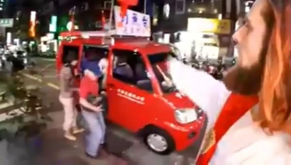 影片中一名身穿白衣留著長髮、絡腮鬍、被網友形容外貿神似「耶穌」的外國男子,指著愛國同心會宣傳車上的五星旗喊「中國狗」。(圖擷取自臉書)