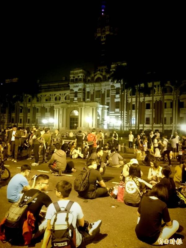 凌晨兩點時,在零星衝突之後,抗議群眾在總統府前席地而坐,軍警人員也保持警戒。(記者王藝菘攝)