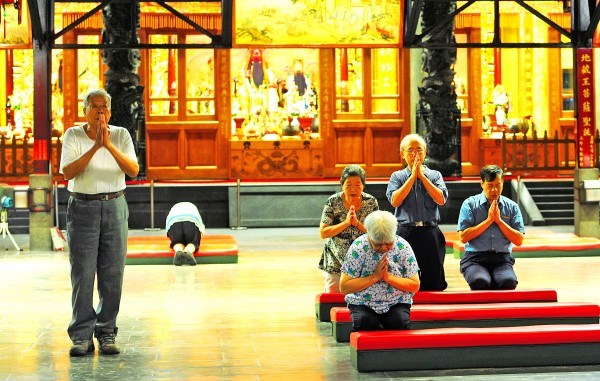 People pray in the Xingtian Temple in Taipei yesterday, after the temple banned incense and offerings of food items. Photo: Lo Pei-der, Taipei Times