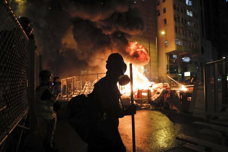示威者在路障淋油點火,現場濃煙竄升到10樓以上。(美聯社)
