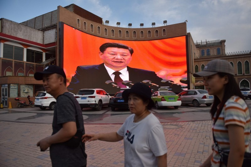 中國新疆維吾爾族自治區喀什市的街道上,一處大螢幕正播放國家主席習近平的談話。(法新社)