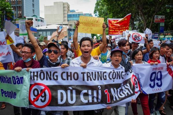 越南人民今聚集在各大城市,手拿標語布條遊行抗議「經濟特區法草案」。(法新社)