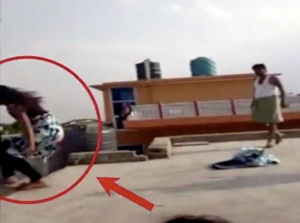 1名12歲的女孩被父親當眾在住處頂樓家暴,女孩不堪父親長期暴力相向,因此從頂樓一躍而下。(圖擷取自影片)