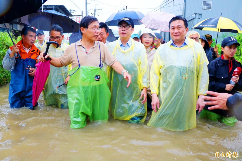 Vice Premier Chen Chi-mai, center, visits a flooded area in Tainan yesterday. Photo: Wan Yu-chen, Taipei Times