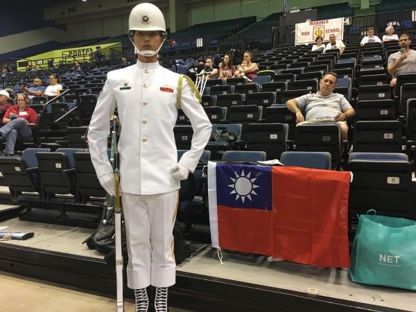 蘇祈麟赴美參加「世界儀隊錦標賽」,與國旗合影。(中央社)