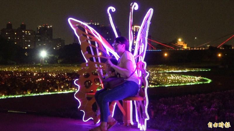 民眾坐在光雕座椅上,彷彿化身為一隻絢麗的蝴蝶。(記者張家寶攝)