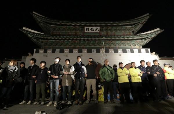 抗議群眾及罹難者家屬聚集在南韓首爾光化門前,外圍並有一排民眾手牽手保護後方靜坐的抗議民眾。