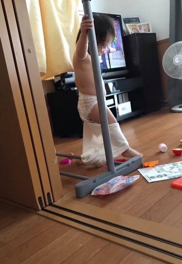 一名網友年幼的女兒上身全裸,下半身褲子脫了一半,右手扶著曬衣架,模樣像極正在跳鋼管舞的脫衣舞孃。(圖擷取自爆廢公社)