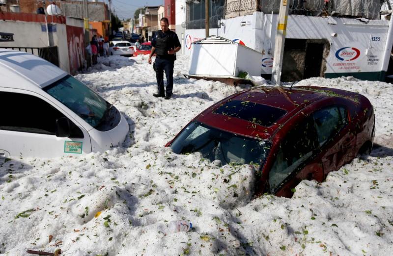 墨西哥第二大城瓜達拉哈拉下起猛烈冰雹,車輛被冰層掩埋。(法新社)