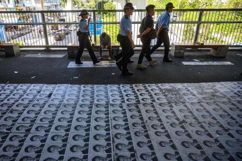 香港親中議員何君堯日前號召民眾今日清理各區連儂牆及塗鴉,隨後疑擔心將引起大風波而取消活動,不過,今早元朗朗屏西鐵站外天橋上,地上貼滿印有何君堯肖像的海報。(法新社)